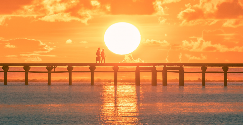 People walking across a bridge with the sun behind them